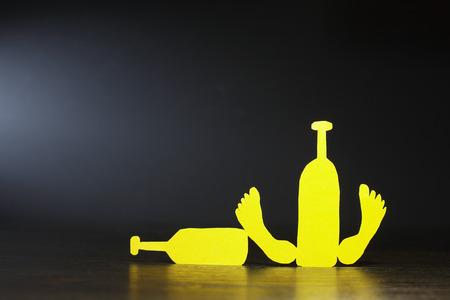 Paper man lying on street with wine bottles against dark background