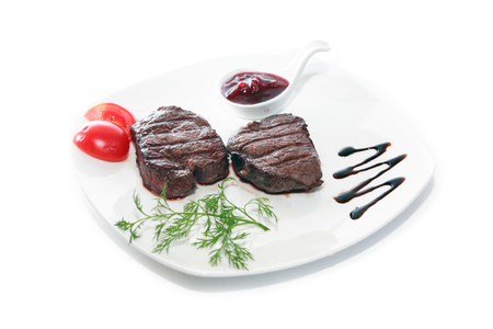 Plate with grilled meat and vegetables on white wooden table Stock Photo