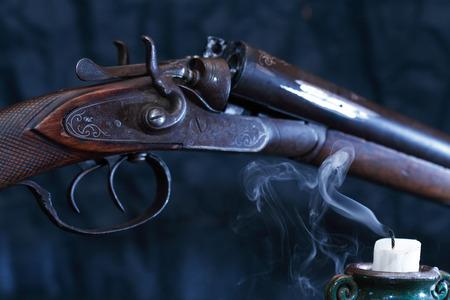 Ancient hunting shotgun closeup near extinguished candle on dark background Stok Fotoğraf