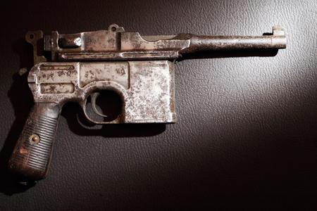gunsight: Old military pistol on dark background under beam of light