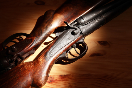 Ancient hunting shotguns closeup on wooden board under light beam