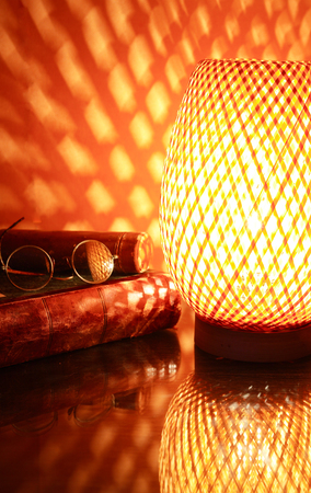 Nice wicker glowing desk lamp near old book against red wall Stock Photo
