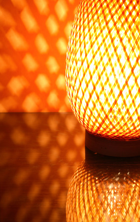 Nice wicker glowing desk lamp with reflection against red wall