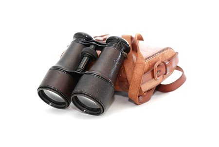 Old binoculars with leather case on white backgkround