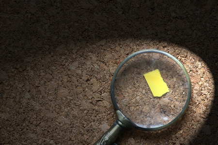 Retro detective concept. Vintage magnifying glass on blank yellow paper on wooden background