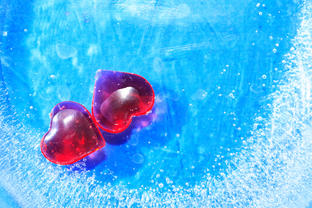 Valentines Day greeting card. Two red hearts in blue frozen water with free space Stock Photo