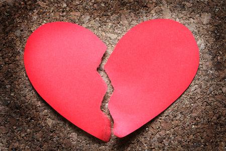 Unhappy love. Red paper broken heart on dark wooden background