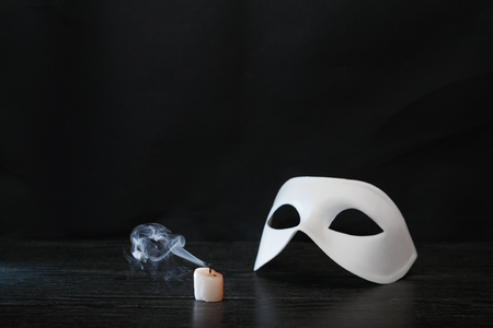 White classical Venetian mask near extinguished candle on dark background Archivio Fotografico