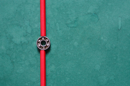 One ball bearing between two red pencils on green background