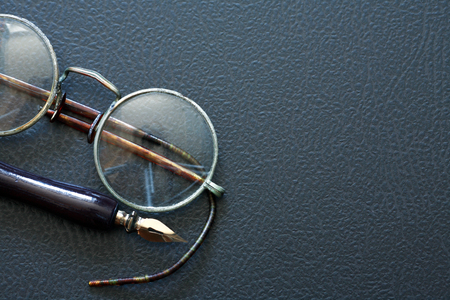 Closeup of old spectacles near pen on dark background