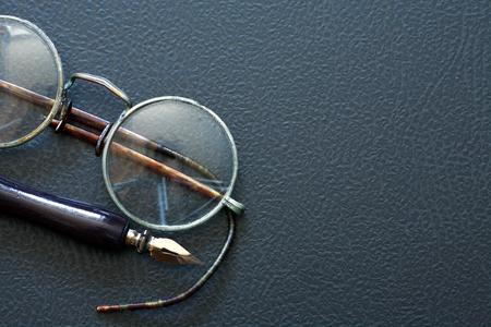 Primer plano de unas gafas antiguas cerca de la pluma sobre fondo oscuro