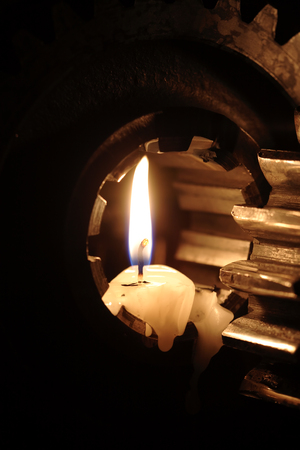 Lighting candles between old gears against dark background