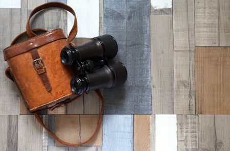 Old binoculars with leather case on color wooden background