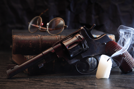 Old revolver near book and extinguished candle