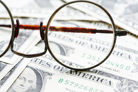 Old spectacles on dollar cash background