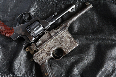 Old revolver and pistol closeup on dark leather background