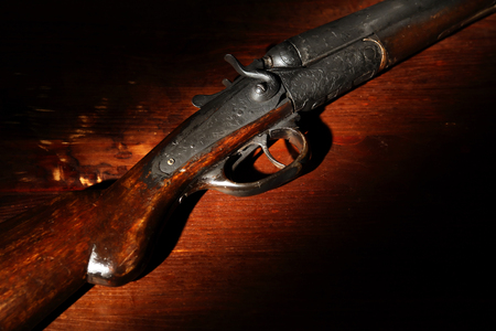 Ancient hunting shotgun closeup on wooden background