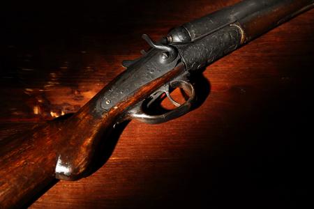Zbliżenie starożytnej strzelby myśliwskiej na drewnianym tle