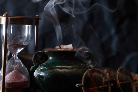Old hourglass and spectacles near extinguished candle with smoke Stok Fotoğraf - 122201888