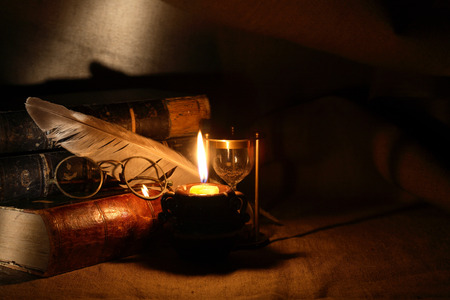 Vintage still life with old glasses against lighting candle and books Archivio Fotografico