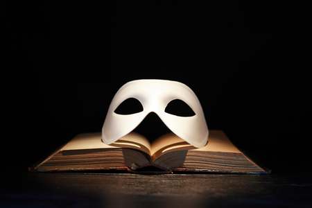 Classical white Venetian mask on old book against dark background Imagens