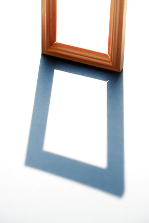 Empty wooden frame with long shadow against sunlight