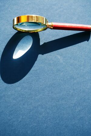 Nice retro magnifying glass under sunlight on gray background 写真素材