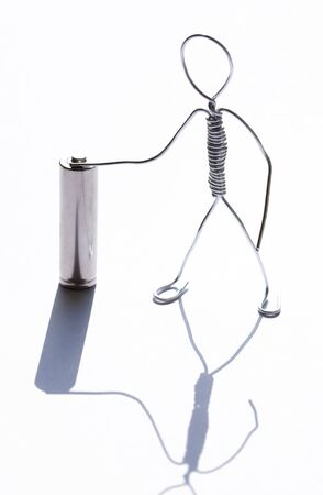 Man made from aluminum wire near old small battery Imagens
