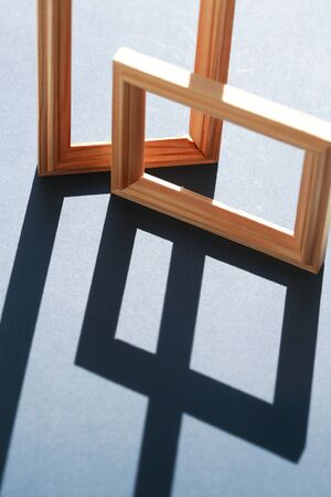 Empty wooden frames with long shadow against sunlight