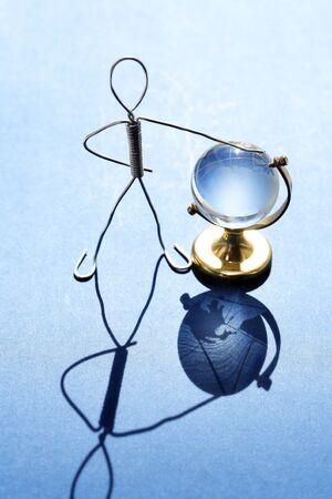Man made from aluminum wire near glass globe 版權商用圖片
