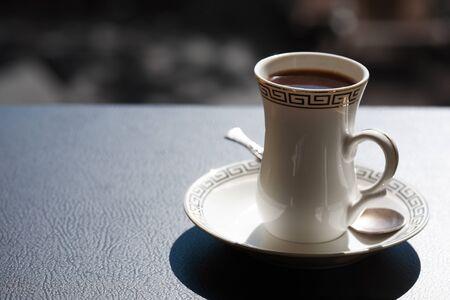 Elegance cup of black coffee under sunlight on dark table