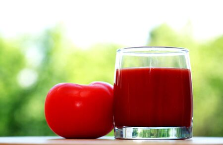 Full glass of tomato juice against nature background 写真素材