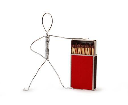 Man made from aluminum wire near open matchbox Фото со стока