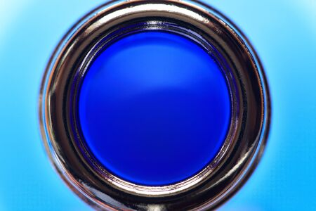 Conceptual background. Top view of the glass bottle neck against blue