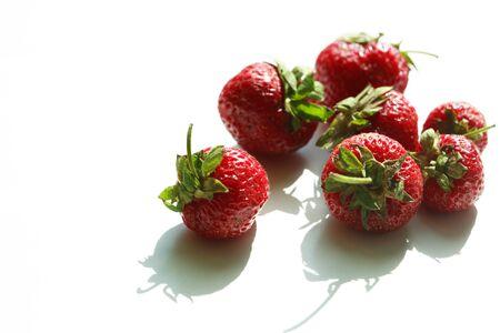 Few strawberry fruits on white against morning sun light