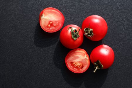 Few red ripe tomatoes against sun light on black background 写真素材