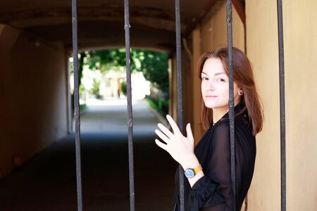 Beauty young woman in front of the old lattice gate in house arch 写真素材 - 129805777