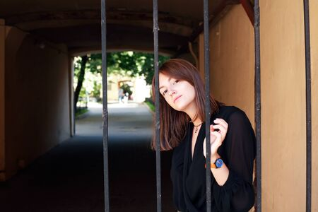Beauty young woman in front of the old lattice gate in house arch 写真素材 - 129805778