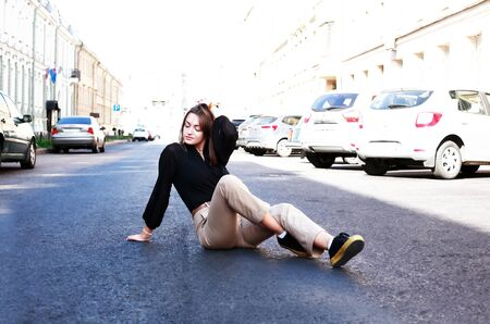 Beautiful young woman sitting on the roadway in the city Stockfoto