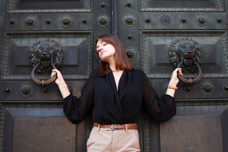 Beautiful young woman near old iron building door 写真素材 - 129790055