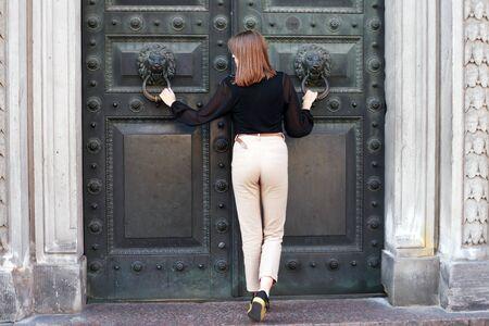 Beautiful young woman near old iron building door