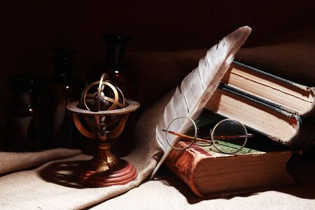 Vintage still life with old books and spectacles on canvas background
