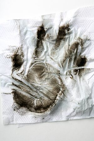 Black dirty handprint on white paper napkin