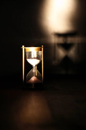 Vintage hourglass on wooden table against dark background with shadow