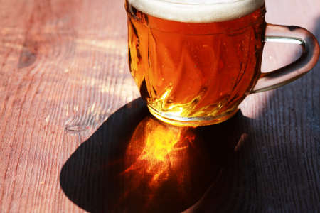 Mug of beer with foam on wooden table under sunlight