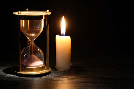 Vintage hourglass near lighting candle on dark background