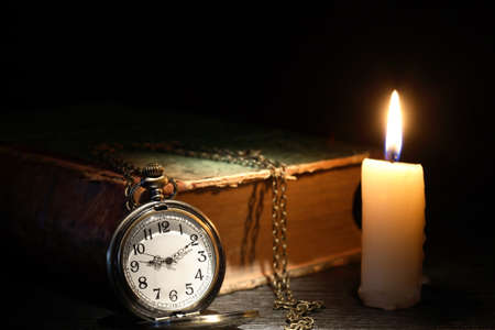 Old pocket watch near old book and candle on dark background