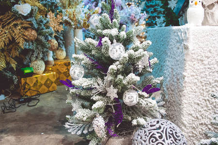 Small Christmas tree decorated with snow. White owl and figured sphere near. Big Christmas trees with garland lights on background.