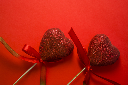 Red background. St. Valentines Day. Red hearts in spangles and with bows. Love. Romanticism.