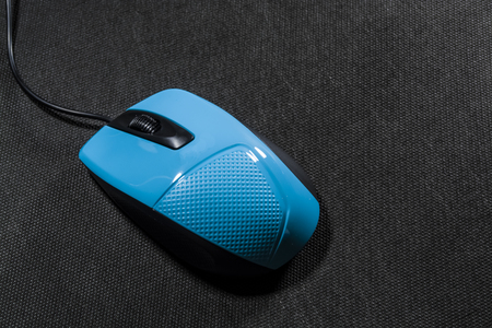 Small computer mouse plastic. Blue color. Black background. Black wire. A blank space for an inscription. Modern technologies. Electronics.